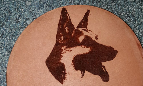 A piece of leather with a dog engraved in it.